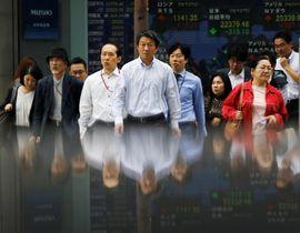 株価ボードの前を歩く人たち=15日、東京都内(ロイター=共同)