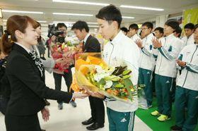 花束を受け取る青山学院大陸上部の選手ら=国東市の大分空港