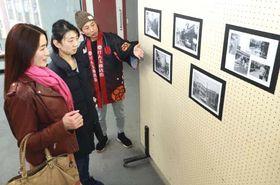 来場者に写真を説明する三好副会長(右)