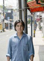 映画を撮影し、現在は生活する新町に立つ映画監督の松田拓真さん=熊本市中央区