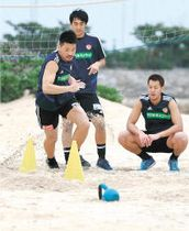 砂浜で体力強化の練習に励む関(左)らGK陣