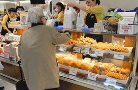 デパートの食品売り場で総菜を購入する高齢者=東京都内の百貨店で