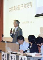 シンポジウムで講演する福島県大熊町の石田仁副町長=21日午後、東京都千代田区