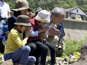 日本海中部地震から35年となり、小学生13人が津波にのまれて亡くなった海岸で手を合わせる人たち=26日、秋田県男鹿市
