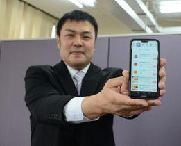 飲食店向けの電子メニューサービスをアピールする田中健代表=4月26日、八戸市内