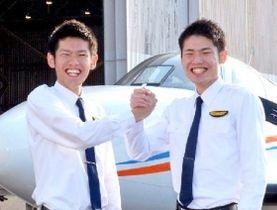 訓練機を背に笑顔の安達航大さん(左)と雄大さん=19日、熊本県菊陽町