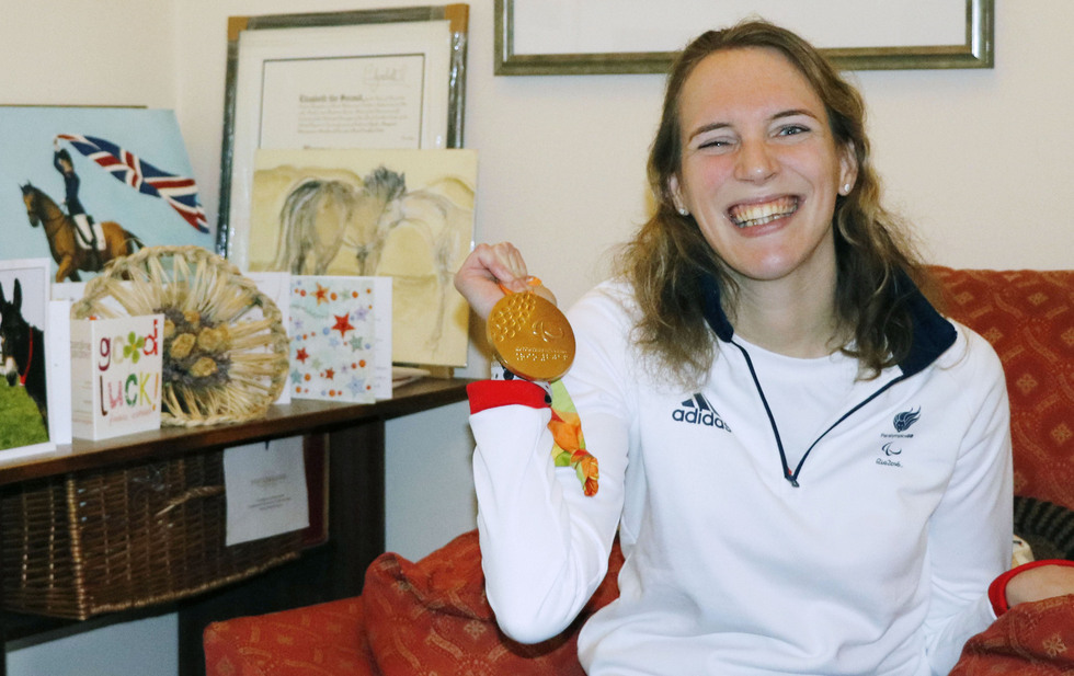 英メイデンヘッドの自宅でパラリンピックのメダルを手に笑顔のソフィー・クリスチャンセン。乗馬の絵や記念品が並ぶ(撮影・原田寛、共同)