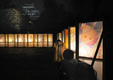 「松江水燈路」で幻想的に浮かび上がるあんどんと松江城(奥)=21日夜、松江市