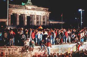 1989年11月9日、東西ドイツの国境開放後にベルリン・ブランデンブルク門前の「ベルリンの壁」の上に立つ人々(DPA提供・AP=共同)