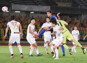 試合終了間際、クロスボールを頭でシュートするDF柳下大樹選手(青色のユニホーム)=富山市南中田で