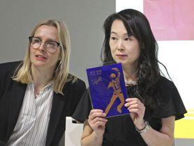 25日、英ロンドンでのイベントで、フィギュアスケートの羽生結弦選手をデザインした「玉虫塗」のカードを紹介する佐浦みどりさん(右)(共同)