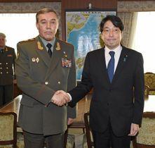 会談前にロシア軍のゲラシモフ参謀総長(左)と握手する小野寺防衛相=11日午後、防衛省