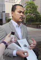 東京高検に署名を提出する前に取材に応じるリンさんの父親レェ・アイン・ハオさん=26日午後、東京・霞が関