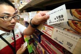消費税増税を前に10%対象商品と示した新しい値札(手前)に付け替える店員=天満屋ハピータウン原尾島店