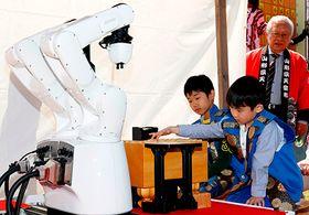 地元の選抜小学生2人が将棋代表ロボット(左)と真剣勝負を展開した「子ども人間将棋」=天童市・舞鶴山