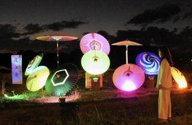 国史跡・上淀廃寺跡で行われたライトアップの試験点灯で、暗闇に浮かび上がった伝統工芸「淀江傘」=17日夜、鳥取県米子市