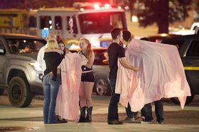 銃乱射事件の現場付近で慰め合う人たち=8日、米カリフォルニア州ロサンゼルス郊外(AP=共同)
