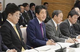 新型コロナウイルス感染症対策本部の会合であいさつする安倍首相(左から2人目)。左端は加藤厚労相=18日午後、首相官邸