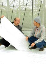 新開発の虫よけシートを手に笑顔を見せる小泉製麻の藤田勇さん(左)と農家の東馬場怜司さん=神戸市北区道場町塩田
