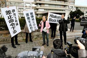 四国電力伊方原発3号機の運転差し止めが決定し、垂れ幕を掲げる住民側=13日午後、広島高裁前