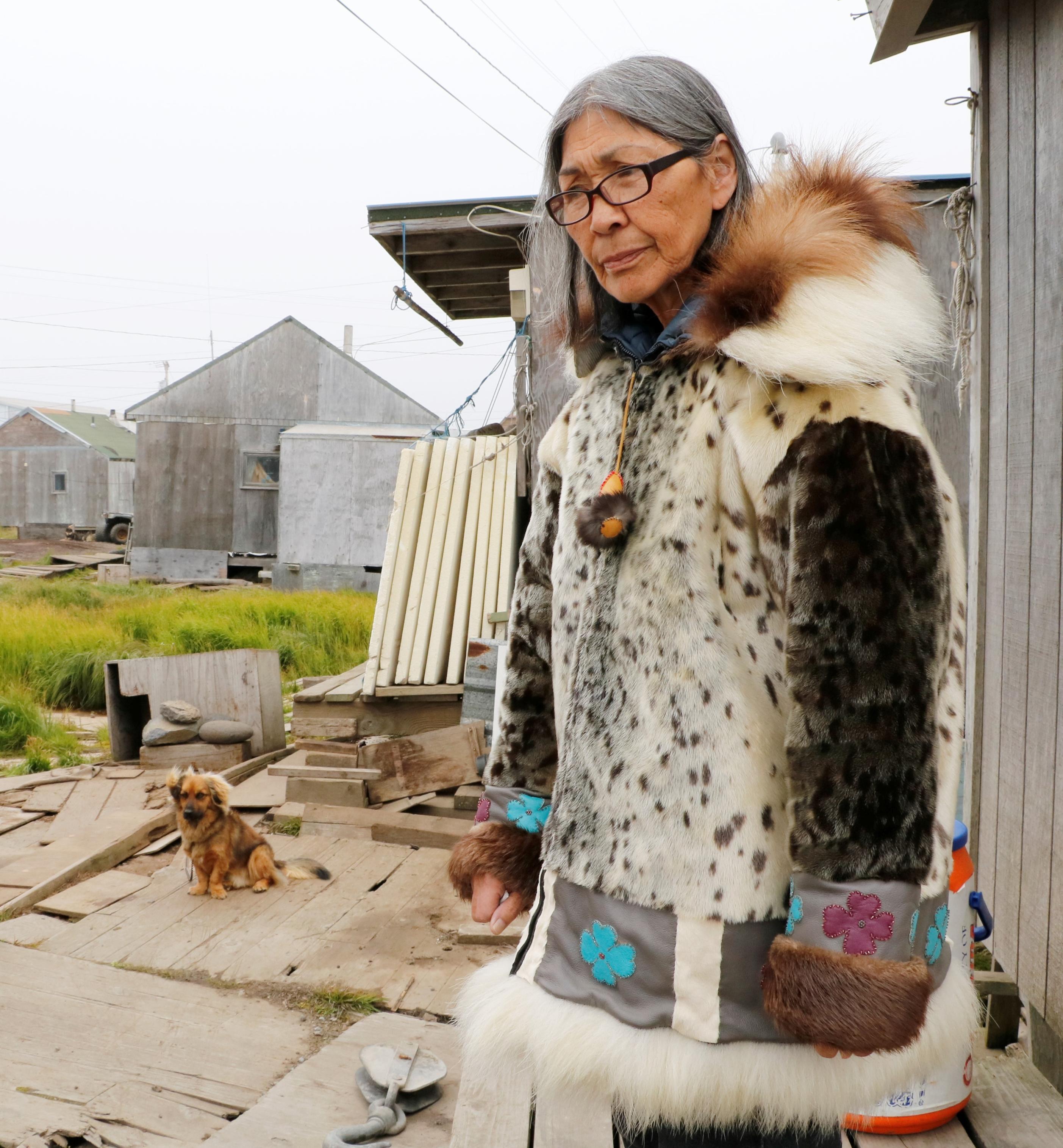 アザラシの皮などで自ら作った服を着て、サボオンガの自宅前に立つクリスティーナ・アロワさん。若い世代にこの服の作り方を教えるのが喜びだという=8月、米アラスカ州・セントローレンス島(共同)
