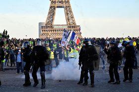 パリのエッフェル塔近くで衝突する警官隊(手前)とデモ隊=23日(アナトリア通信・ゲッティ=共同)
