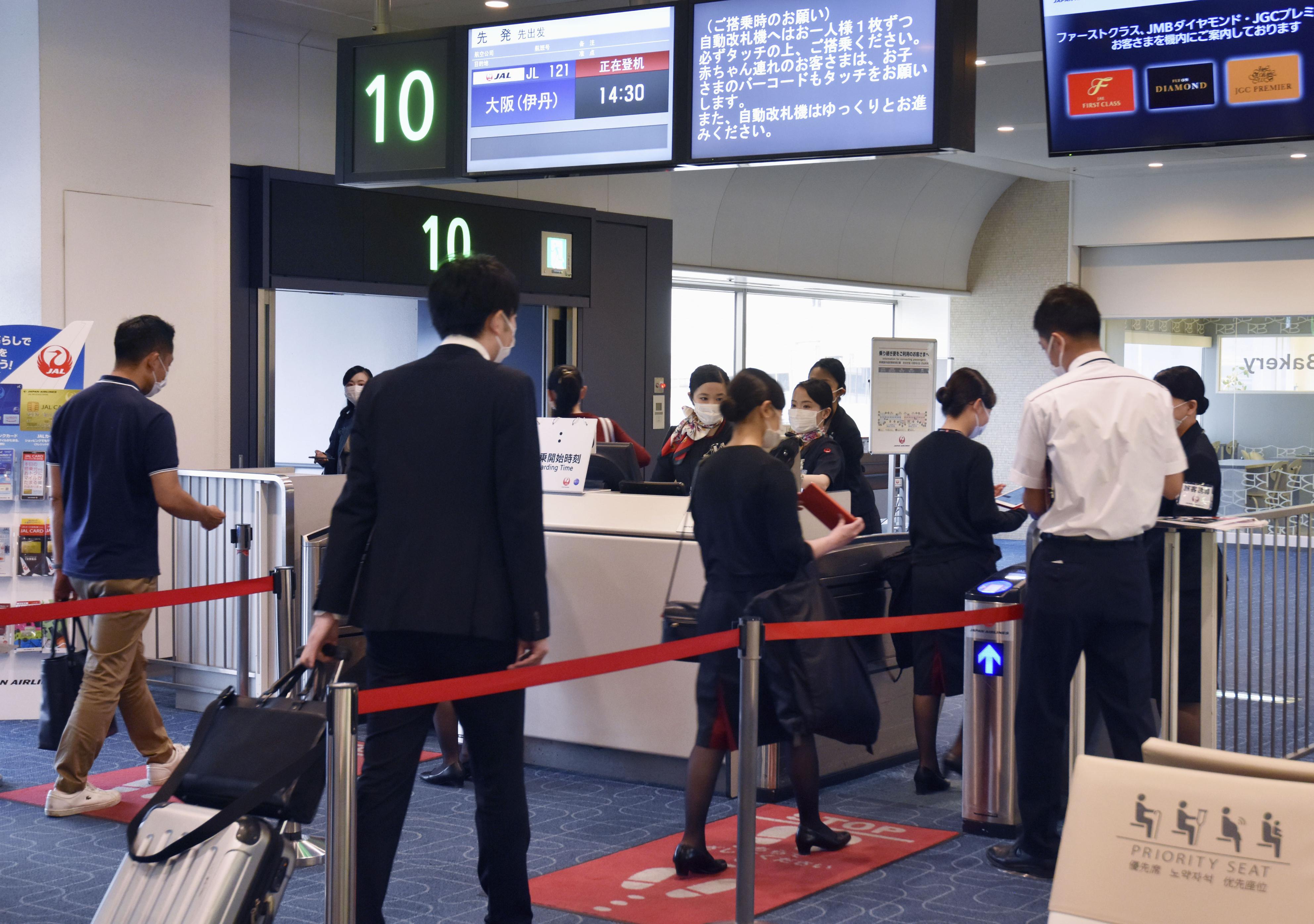 新型コロナウイルスの感染防止の徹底を呼び掛ける日航の地上スタッフ=1日午後、羽田空港