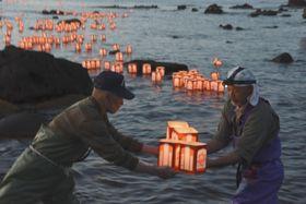北海道南西沖地震の犠牲者を悼む「賽の河原祭」で灯籠を海に流す島民=22日午後、北海道・奥尻島