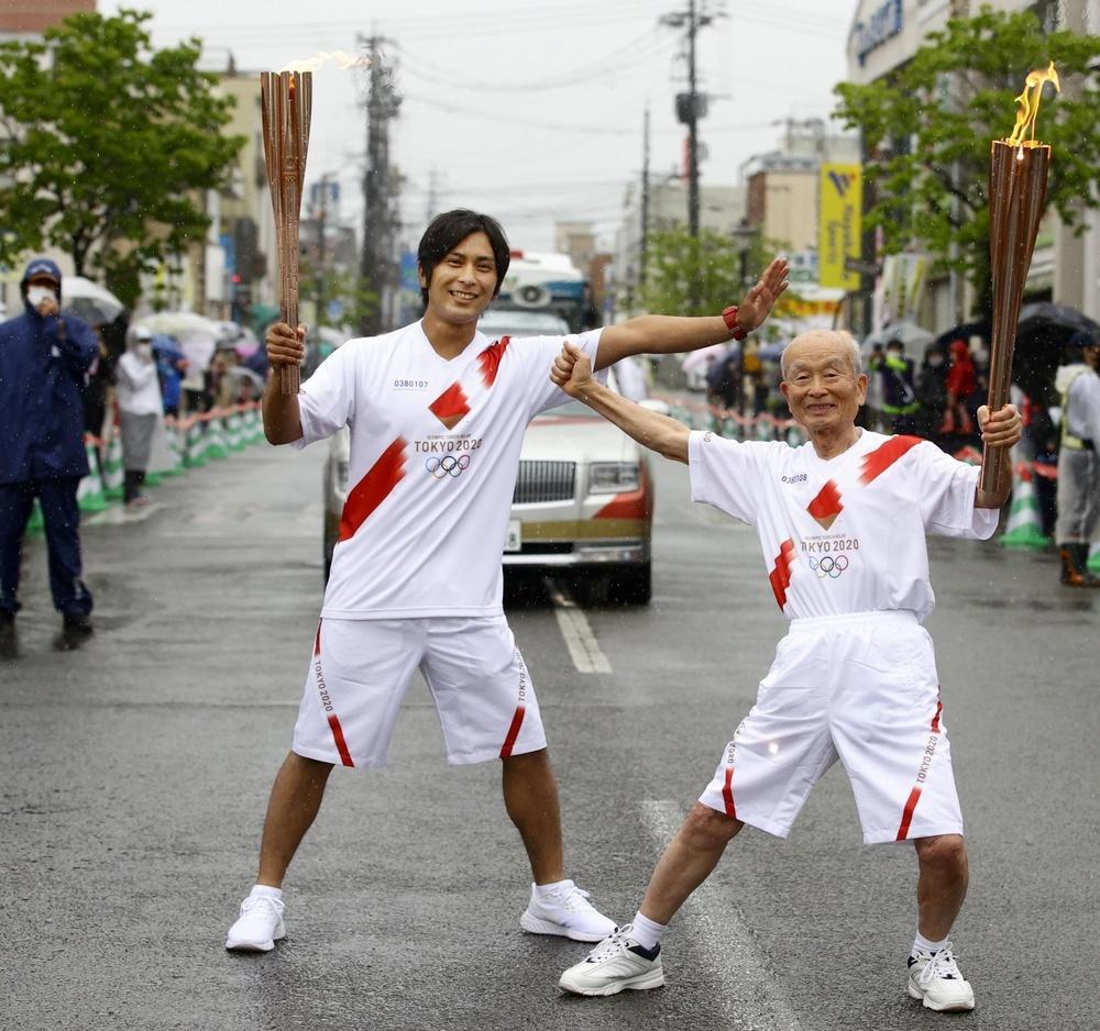 次走者(右)に聖火を引き継ぎ、ポーズをとる堺大誉さん=5日午前、熊本県人吉市