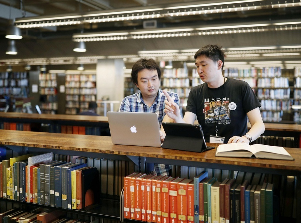 北米ウィキカンファレンスの会場となった図書館でパソコンを前に語り合う、中国語版ウィキペディアの管理者トミー・トン(右)とジミー・シュウ=米サンディエゴ(撮影・遠藤弘太、共同)