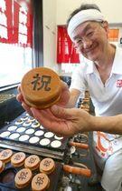 「祝」の焼き印が入った大判焼きを手にする高橋道明さん(阿部裕貴撮影)