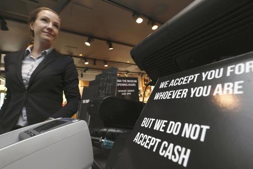 「アバ博物館」で受け付けカウンターに書かれた「現金は受け取れません」の表示をアピールする博物館長(左)=5月、ストックホルム(共同)