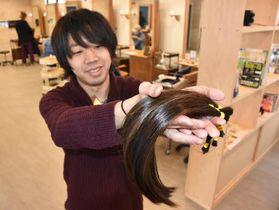 がん患者のために寄付された髪を見せる「カノエ」のスタッフ(山口市)