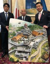 水原一夫さん(中央)と俊彦さん(左)が県に寄託した安土城の天主とその周辺を描いた油絵=大津市・県庁