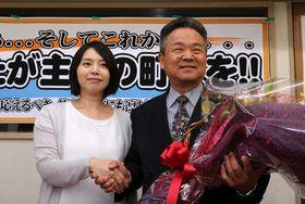 3選を果たし、親族から花束を受け取る山口さん(右)=9日午後8時42分、川棚町栄町の選挙事務所