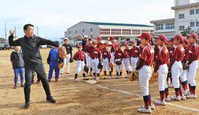 小学生に野球を指導する田畑一也さん(左)=高岡市二塚小で