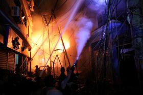 21日、ダッカで消火活動に当たる消防士ら(ロイター=共同)
