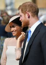 22日、ロンドンのバッキンガム宮殿の庭園で開かれたパーティーに出席した英王室のヘンリー王子とメーガン妃(ロイター=共同)