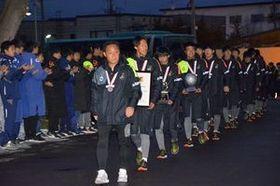 学校に到着し、生徒たちに温かく出迎えられる黒田監督と選手ら=14日午後4時50分、青森市の青森山田高校