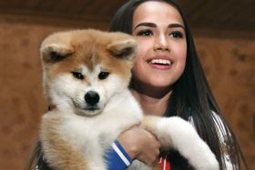 贈呈された秋田犬の子犬を抱き、笑顔のアリーナ・ザギトワ選手=26日、モスクワ(共同)