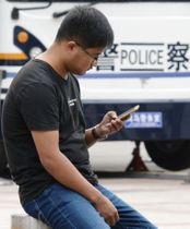 北京市内の繁華街でスマートフォンを見る男性=14日(共同)