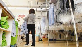 過酷な労働条件の下で働くクリーニング店の店主=東京都内で(芹沢純生撮影)