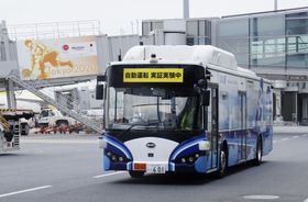 実証実験で制限区域を走行する大型バス=22日、羽田空港
