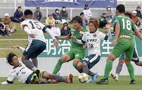 【ヴァンラーレ八戸-SC相模原】前半、敵陣でボールを取り合うヴァンラーレ(緑)の選手ら=14日、八戸市のダイハツスタジアム