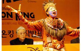 韓国版「ライオンキング」の制作発表をする劇団四季の浅利慶太氏(後方)と歌を披露する出演者=ソウル市内、2006年6月