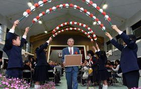 児童によるアーチをくぐり退場する福田康博校長=鹿屋市の南小学校