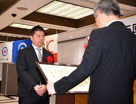 贈呈式で柴田建哉社長(手前)から賞状を受けるラグビーW杯日本代表の藤井強化委員長