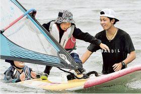 子どもにウインドサーフィンを教える石井さん(右)=御前崎市のマリンパーク御前崎