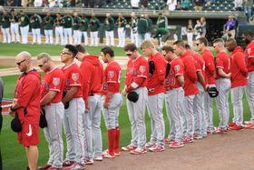 銃撃事件で亡くなった生徒たちを悼み、黙とうする米大リーグ、エンゼルスの選手(手前)とアスレチックスの選手ら=23日、米アリゾナ州メサ(共同)