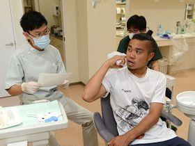 歯科医師の問診を受ける田中パウロ淳一選手(右)=岐阜市加納城南通、県歯科医師会館